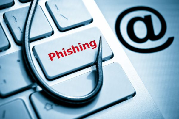 phishing / fish hook on computer keyboard with email sign